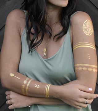 gold tattoo auf oberarm und unterarm