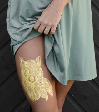 Gold Tattoo auf Oberschenkel Bein